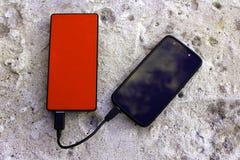 Rotbraunes powerbank und Smartphone auf konkretem Hintergrund Lizenzfreies Stockbild