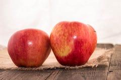 Rote Äpfel auf einem rustikalen Hintergrund Lizenzfreie Stockbilder
