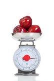 Rote Äpfel auf einer Skala auf Weiß Stockfotografie