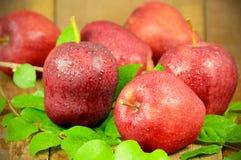 Rote Äpfel auf hölzernem Hintergrund Stockfotografie