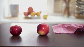 Rote Äpfel auf hölzerner Tabelle Übergeben Sie dem Setzen reife rote Äpfel auf einen Holztisch stock video footage