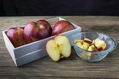 Rote Äpfel in der Schüssel und Äpfel im Kasten auf dem Holztisch Lizenzfreies Stockbild