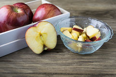 Rote Äpfel in der Schüssel und Äpfel im Kasten auf dem Holztisch Stockfoto