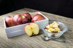 Rote Äpfel in der Schüssel und Äpfel im Kasten auf dem Holztisch Stockbilder