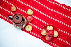 Rote Äpfel in einer Schüssel auf einer fantastischen Wolldecke Stockfotos