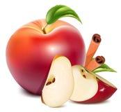 Rote Äpfel mit grünen Blättern und Zimt. Stockfotografie
