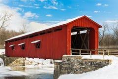 Rote überdachte Brücke mit Schnee Stockbild