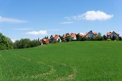 Rote überdachte Häuser auf einem grünen Hügel Lizenzfreie Stockbilder
