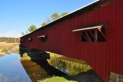 Rote abgedeckte Brücke über Fluss Stockbild