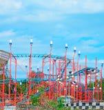 Rote Achterbahn unter einem blauen Himmel Lizenzfreie Stockfotos