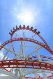 Rote Achterbahnschiene mit blauem Himmel im Hintergrund Stockfotografie