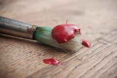 Rote Acrylfarbe auf Bürste auf Holztischhintergrund Lizenzfreie Stockbilder