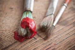 rote Acrylfarbe auf Bürsten auf Holztisch backgrou Stockbilder