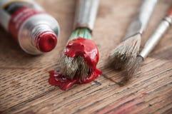 rote Acrylfarbe auf brusches auf Holztisch backgro Lizenzfreies Stockbild