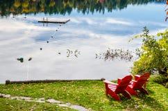 Rote Adirondack-Stühle auf dem Ufer von einem See Stockbild