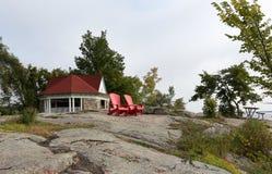 Rote Adirondack-Stühle auf einem Granithügel Lizenzfreies Stockfoto
