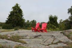 Rote Adirondack-Stühle auf einem Granithügel Lizenzfreie Stockfotografie