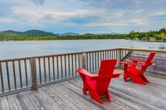 Rote Adirondack-Stühle auf Lake Placid-Plattform Stockfotografie