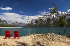 Rote Adirondack-Stühle am See Minnewanka Stockfoto