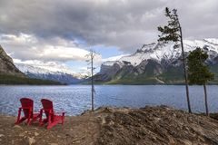 Rote Adirondack-Stühle am See Minnewanka in Nationalpark Banffs Stockfotos