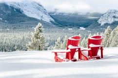 Rote Adirondack-Stühle vor einem Snowy-Tal Stockbilder