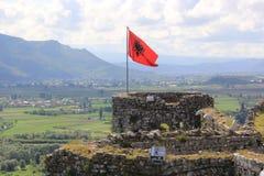 Rote albanische Flagge mit einem doppelköpfigen schwarzen Adler, der über die Spitze der alten Festung Rozafa wellenartig bewegt Stockbilder