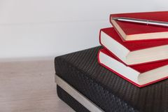 Rote alte Bücher auf einem Schreibtisch mit einem weißen Hintergrund Stockbild