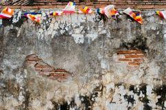 Rote alte Backsteinmauer mit bunten Flaggen Lizenzfreie Stockbilder