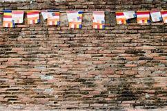 Rote alte Backsteinmauer mit bunten Flaggen Stockfoto