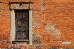 Rote alte Backsteinmauer mit einer schwarzen Tür Altes factur Lizenzfreie Stockfotografie