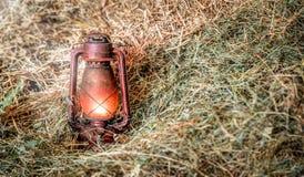 Rote alte beleuchtete Lampe im Heu Stockfotografie