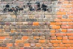 Rote alte getragene Backsteinmauer mit schwarzen Flecken masern Hintergrund Lizenzfreies Stockfoto