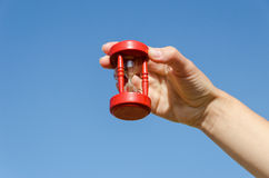 Rote alte Sanduhr in der Hand auf Hintergrund des blauen Himmels Stockbild