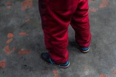 Rote Arbeitskleidungshosen auf konkretem Hintergrund des Schmutzes lizenzfreies stockbild