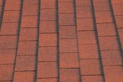 Rote Asphaltschindeln auf Haus Stockfotografie