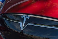 Rote Autohaubenabdeckung mit Tesla-Logonahaufnahme stockbild