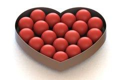 Rote Bälle in Herz-geformtem Metallkasten lizenzfreie stockbilder