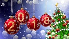 Rote Bälle mit den Nr. 2018, die am Hintergrund eines blauen bokeh und des drehenden Weihnachtsbaums hängen stockbild