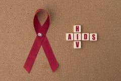 Rote Bänder unterstützt Band mit AIDS-/HIVwort auf Anschlagtafel Stockbilder