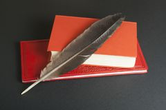 Rote Bücher und Federkiel auf schwarzem Hintergrund getrennte alte Bücher Stockfoto