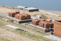 Rote Backsteine gestapelt in den Stapel an der Baustelle Lizenzfreie Stockfotos