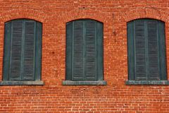 Rote Backsteinmauer mit drei hölzernen grünen Fenstern Lizenzfreies Stockbild