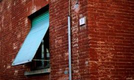 Rote Backsteinmauer mit geöffnetem Fenster Lizenzfreie Stockbilder
