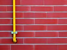 Rote Backsteinmauer mit gelbem Rohr Stockbild
