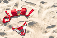 Rote Badebekleidung auf Sand. Feiertage und Ferien. Stockbilder