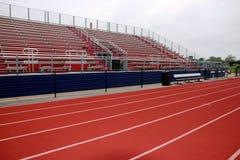 Rote Bahn vor den roten und blauen Zuschauertribünen stockbild