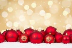 Rote Balldekoration der Weihnachtskarte mit goldenem Hintergrund Lizenzfreies Stockbild