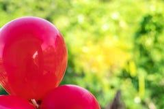 Rote Ballone auf einem bokeh Baumhintergrund unter Verwendung der Tapeten oder der Hintergründe für ein festliches Ereignis Stockbilder