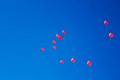Rote Ballone, die auf den Himmel fliegen Stockfotos