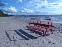 Rote Bank auf dem Strand Stockfotografie
